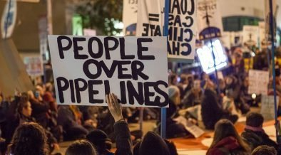 Protesters against the Dakota Access Pipeline and Keystone XL Pipeline hold a sit-in in the street next to the San Francisco Federal Building.