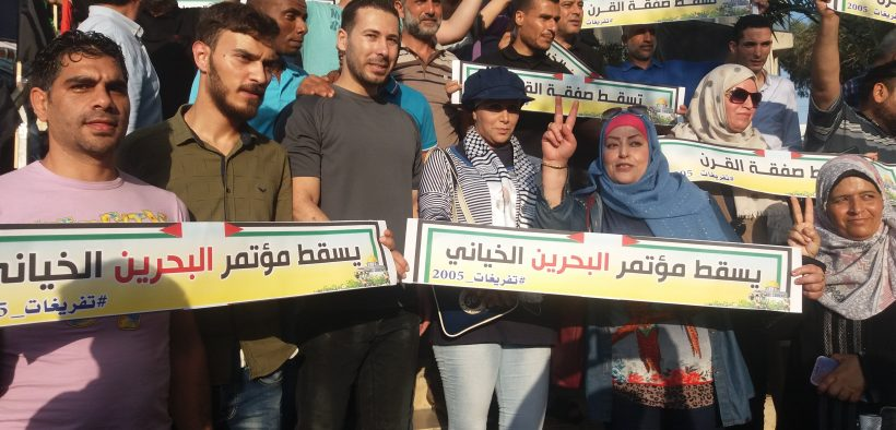 """Palestinian protesters hold signs reading """"Down to the Bahrain Treason Conference."""" They are crowding outside of the Gaza-based Rashad Alshawa Cultural Center. Tuesday, June 25, 2019. (Photo: Rami Almeghari, Gaza)"""