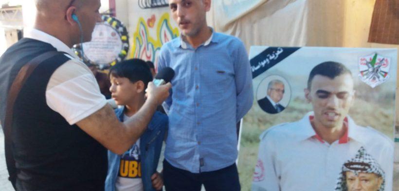 Mohammad Alserhy, de goede vriend van Mohammad Aljadeely, voor de deur van het huis van de Aljadeely in het vluchtelingenkamp Alburaij. Rechts van hem staat een portret van Mohammad Aljadeely. (Foto: Rami Almeghari)