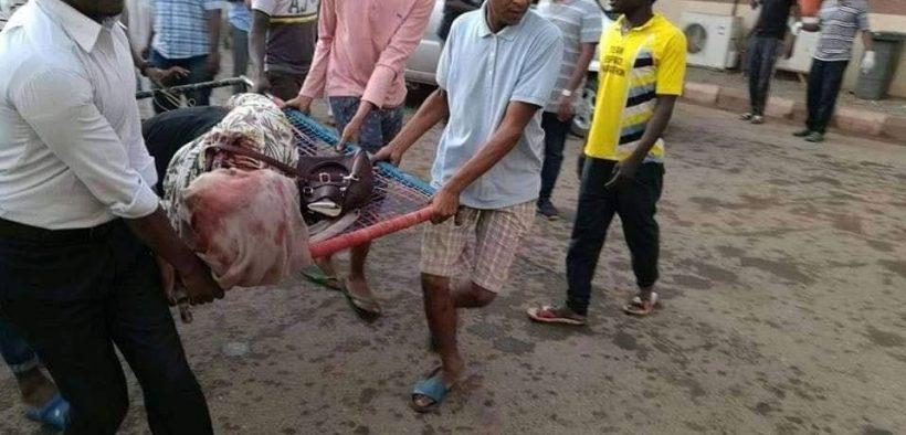 Protestors carrying an injured woman during Khartoum massacre.
