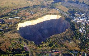Яма в Премьер Майн, Куллинан, Гаутенг, Южная Африка. Площадь поперечного сечения ямы глубиной в 190 на его поверхности составляет около гектара 32. [1] Шахта была источником алмаза Куллинан карат 3106, самого большого алмаза из когда-либо найденных.
