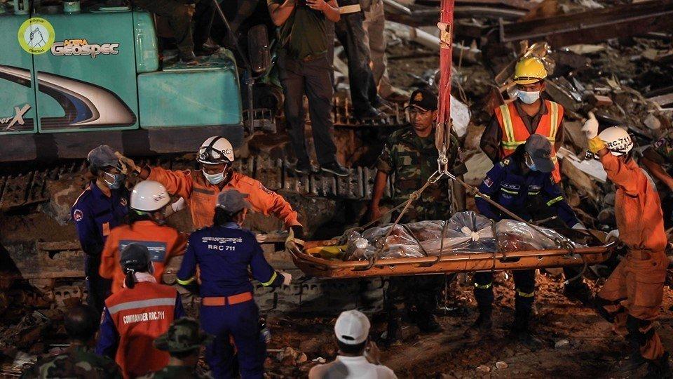 عمال الإنقاذ في موقع انهيار المبنى المميت في سيهانوكفيل ، كمبوديا في يونيو (تصوير CENTRAL).