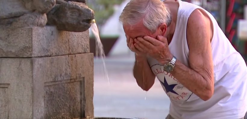 A man attempts to cool off at a water fountain as a heat wave strikes Europe. (Photo: YouTube screenshot)