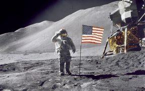 """O astronauta David R. Scott, comandante, faz uma saudação militar ao lado da bandeira americana durante a atividade extraveicular da superfície lunar (EVA) da Apollo 15 no local de pouso Hadley-Apennine. A bandeira foi implantada no final do EVA-2. O Módulo Lunar """"Falcon"""" é parcialmente visível à direita. Hadley Delta no fundo sobe aproximadamente 4,000 metros (cerca de 13,124 pés) acima da planície. A base da montanha é de aproximadamente 5 quilômetros (cerca de 3). Esta fotografia foi tirada pelo astronauta James B. Irwin, piloto do Lunar Module"""
