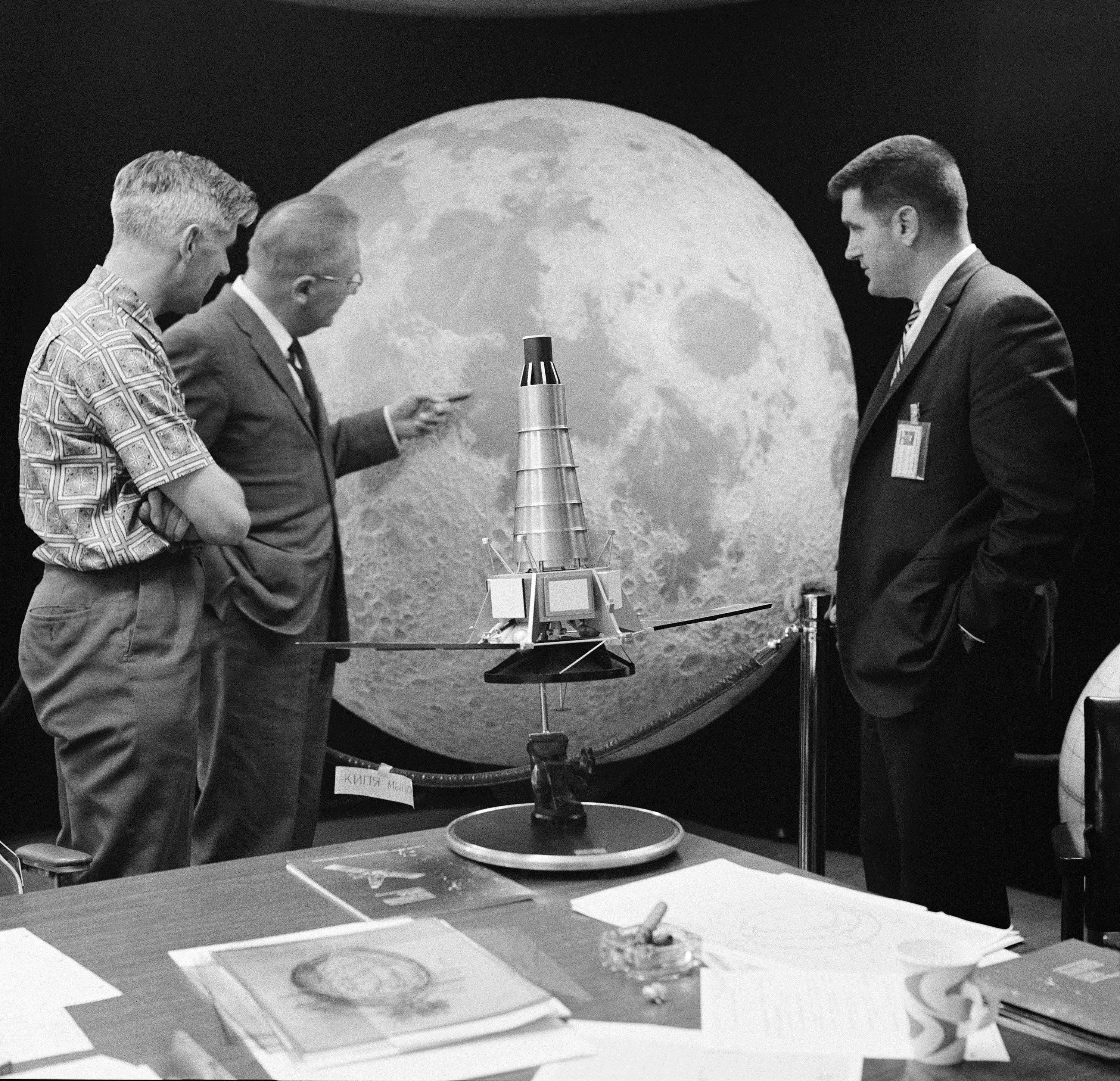 Three members of the Ranger 7 television experiment team stand near a scale model and lunar globe. From left: Ewen Whitaker, Dr. Gerard Kuiper, and Ray Heacock.
