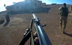 Militants of Hayat Tahrir al-Sham (HTS) fighters storm the village of Mushairfa, northeast of Hama, during the Northeastern Hama offensive (2017). The Image is part of a video taken by a helmet camera.