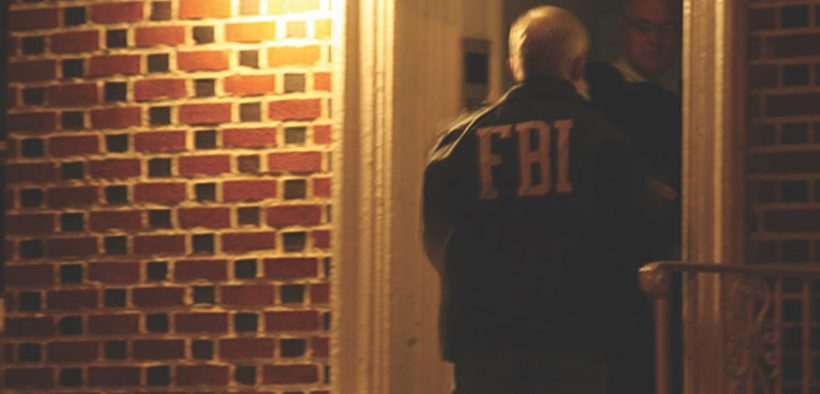 An FBI agent knocks on a door in Brooklyn in 2011 as part of a raid on N.Y. mafia. (Photo: FBI)