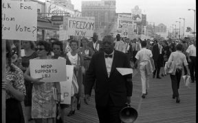 """African American and white Mississippi Freedom Democratic Party supporters holding signs reading """"Freedom now"""" and """"MFDP supports LBJ"""" while marching on the boardwalk at the 1964 Democratic National Convention, Atlantic City, New Jersey"""