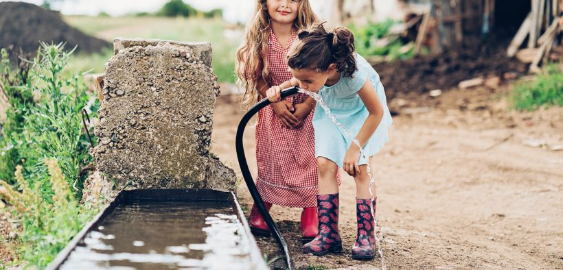 Two children drinking water outdoors. An estimated 110 million Americans are potentially exposed to PFAS through drinking water.