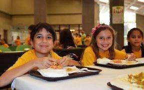 Tre bambini si godono il pranzo preparato al momento e servito in loco da una società di gestione dei servizi alimentari presso l'Inter Metro Summer Recreation Program a San Juan, Portorico.
