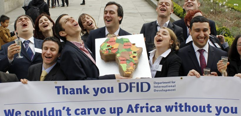 WDM campaigners dressed as business people from Monsanto, Diageo, SABMiller and Unilever deliver a cake to the Department for International Development to thank the UK government for its support to allow them to carve up Africa.