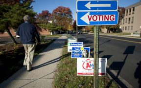 A voter walks past candidate signs on election day 2014.