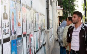 A Tunisian voter peruses one of the many officially designated walls where parties were permitted to present their campaign posters during Tunisia's 2011 election. More than 65 parties and independent lists competed for seats in the constituent assembly