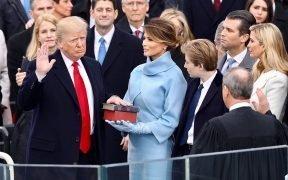 Президент Дональд Трамп приведен к присяге в январе 20, 2017 в здании Капитолия в Вашингтоне, округ Колумбия. Мелания Трамп носит небесно-голубой кашемировый ансамбль Ральфа Лорена. Он держит левой рукой две версии Библии, одну детскую Библию, подаренную ему его матерью, вместе с Библией Авраама Линкольна.