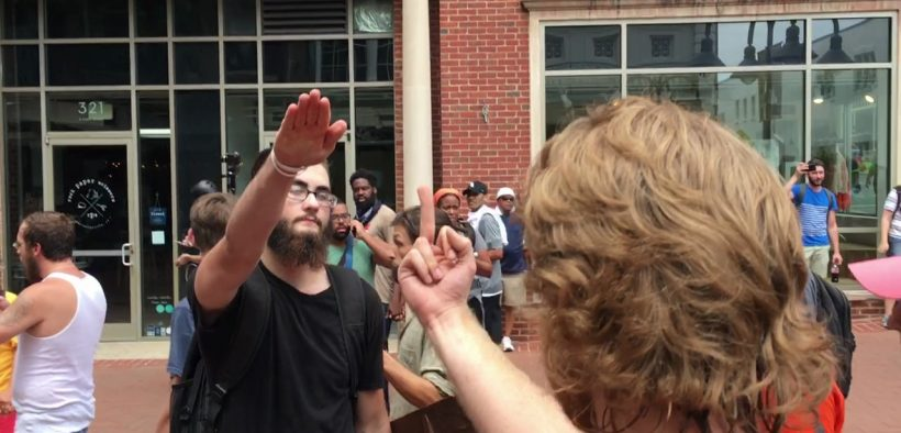 A counter-protester gives a white supremacist the middle finger. The white supremacists responds with a Nazi salute. Charlottesville August 12, 2017.