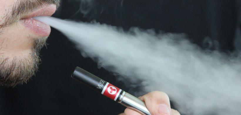 man vaping exhaling smoke