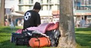 A homeless man sits in the shade with his belongings at Venice Beach. Apple's pledge to stem California's housing crisis is being criticized for not tackling homelessness.