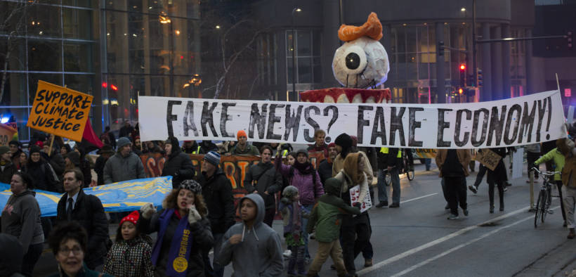 """Protesters hold sign saying """"fake news? fake economy! during January 2017 protest of Donald Trump inauguration."""