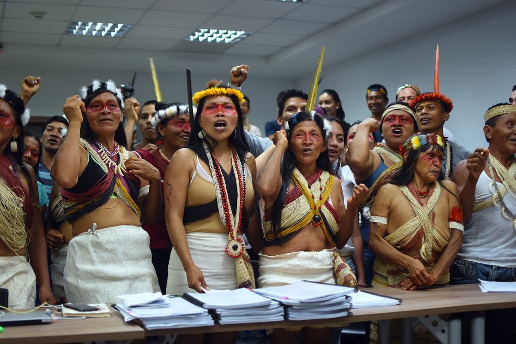 The Waorani people sing after a long hearing as they await a three-judge panel ruling at a Provincial Court in Pastaza, Ecuadorian Amazon. (Photo credit: Amazon Frontlines)