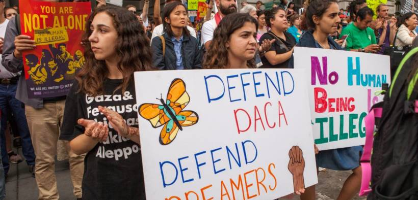 Protesters hold various signs and banners at a DACA rally in San Francisco.