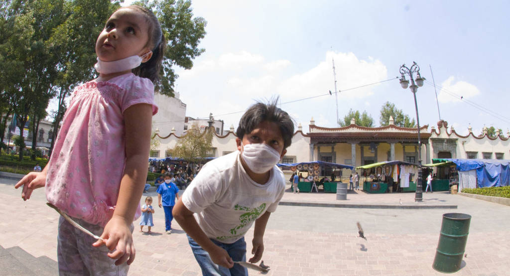 Children in Mexico wear masks during the 2009 swine flu outbreak. New flu pandemics are just one of the many public health crises linked to factory farming. (Photo credit: sari huella/Wikimedia Commons)