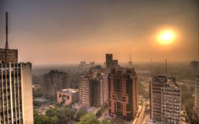 Sun setting at Connaught Place in Delhi. The air was so full of smog particles that the sun often disappeared completely into the fog. View from the revolving Parikrama rooftop restaurant. November 2006.