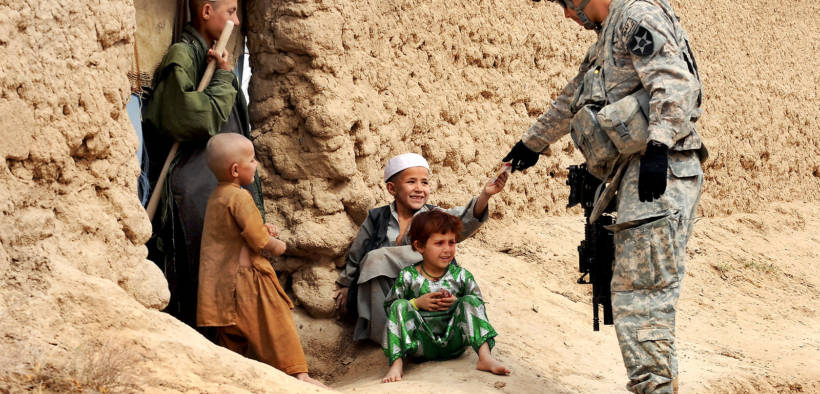 U.S. Army Sgt. Jose Gonzalez gives snacks to Afghan children during a patrol in Dagyan village in Helmand province, Afghanistan, Feb. 21, 2010. Gonzalez is assigned to Company C, 4th Battalion, 23rd Infantry Regiment. U.S. Air Force photo by Staff Sgt. Christine Jones