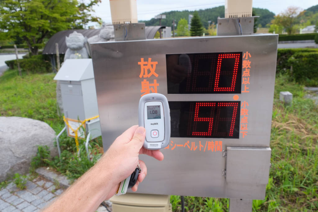 Author comparing the readings of handheld geiger counter with official monitoring post in Iitate, Fukushima Prefecture. Date: Aug. 2013. (Photo: Miguel Quintana)