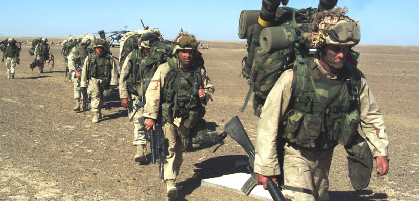 A US Marine with the 15th Marine Expeditionary Unit leads others to a security position after seizing a Taliban forward-operating base November 25, 2001