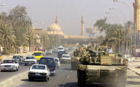A Marine Corps M1 Abrams tank patrols a Baghdad street after its fall in 2003 during Operation Iraqi Freedom.