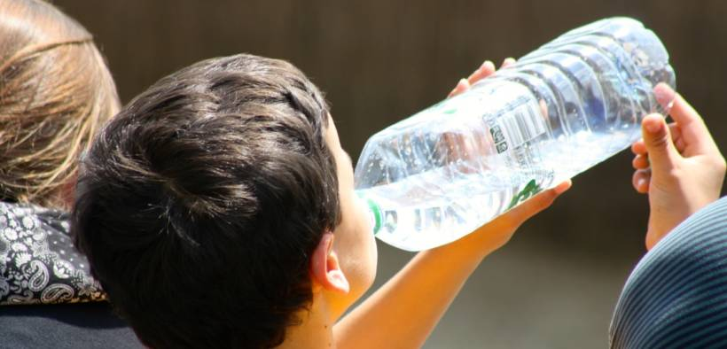 child drinking from a plastic water bottle